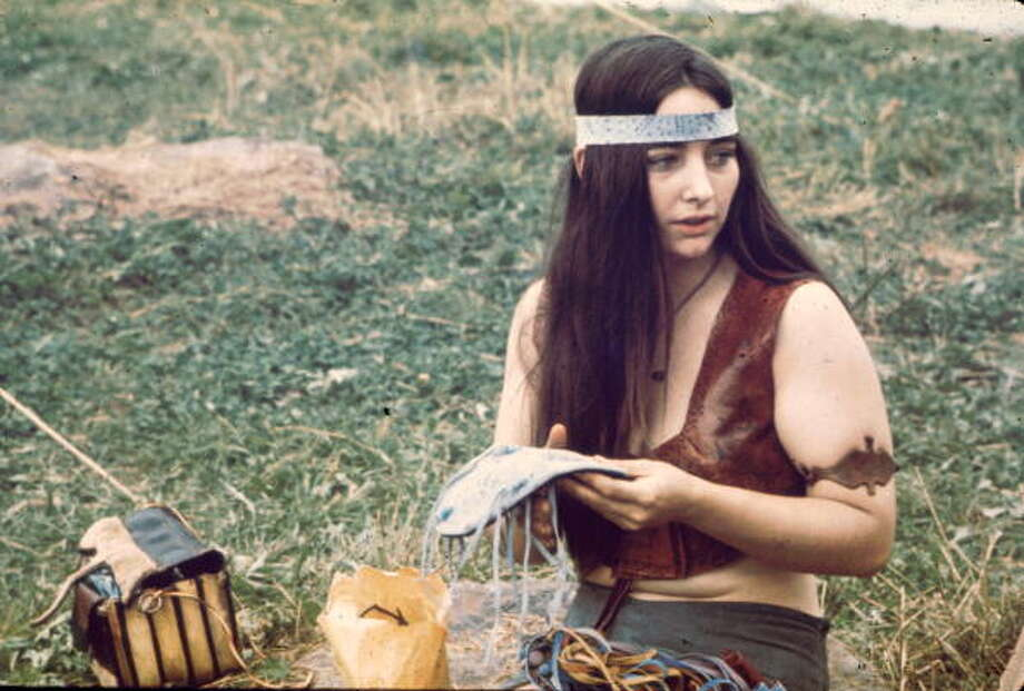 Close-up of a young woman as she kneels on the grass, a leather craft in her hands, near the 'Free Stage' at the Woodstock Music and Arts Fair, Bethel, New York, August 1969. She is dressed in a leather vest with a matching armband, and a headband. The 'Free Stage' essentially functioned as both a place from the scheduled performers to jam and as an open mic stage for festival goers. The festival ran from August 15 to 18. Photo: Ralph Ackerman, (Getty Images) / Hulton Archive