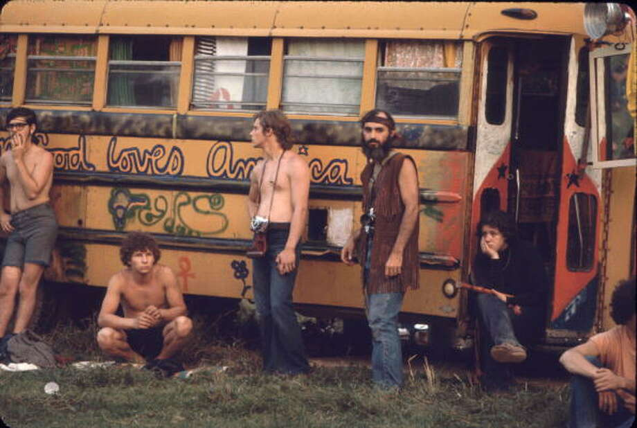 Near the 'Free Stage' at the Woodstock Music and Arts Fair, several men, two with cameras around their necks, lean against a decorated school bus used by the Hog Farmers, a group who had been asked to help construct, ensure security, and provide food for the event, Bethel, New York, August 1969. The 'Free Stage' essentially functioned as both a place from the scheduled performers to jam and as an open mic stage for festival goers. The festival ran from August 15 to 18. Photo: Ralph Ackerman, (Getty Images) / Hulton Archive
