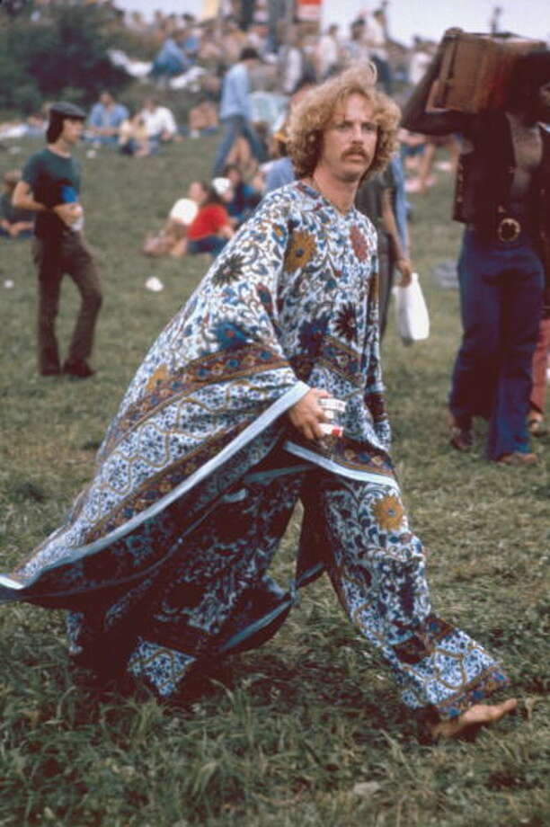An unidentified, mustachioed young man, barefoot but dressed in a flowered kaftan, carries what appears to be three packs of cigarettes as he strides through the grass at the Woodstock Music and Arts Fair in Bethel, New York, August 15 - 17 (and part of the 18th), 1969. Photo: Bill Eppridge, (Getty Images) / Time & Life Pictures