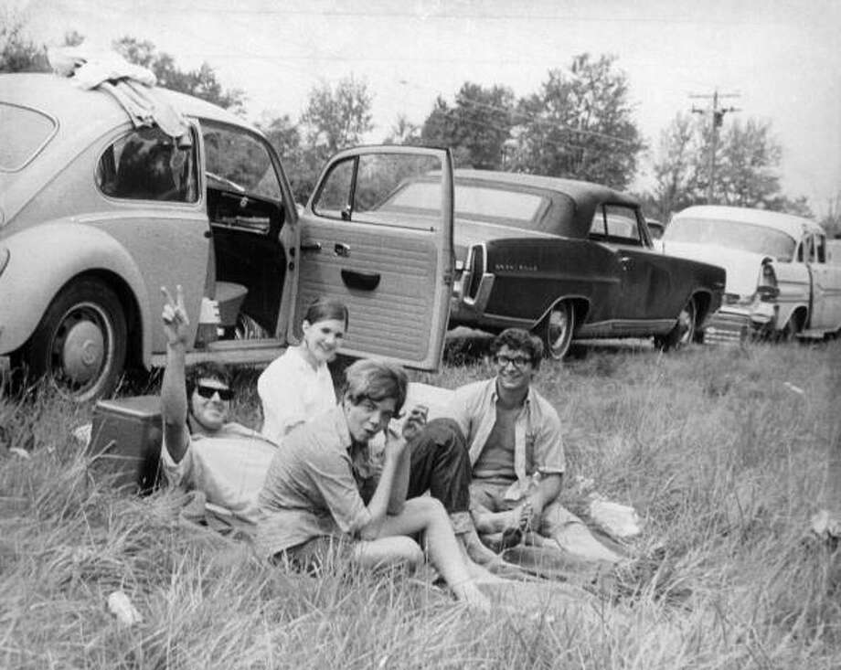 August 1969:  A group of friends sitting by their car at the Woodstock Music and Arts Fair, one of them is giving a peace sign. Photo: Three Lions, (Getty Images) / Hulton Archive