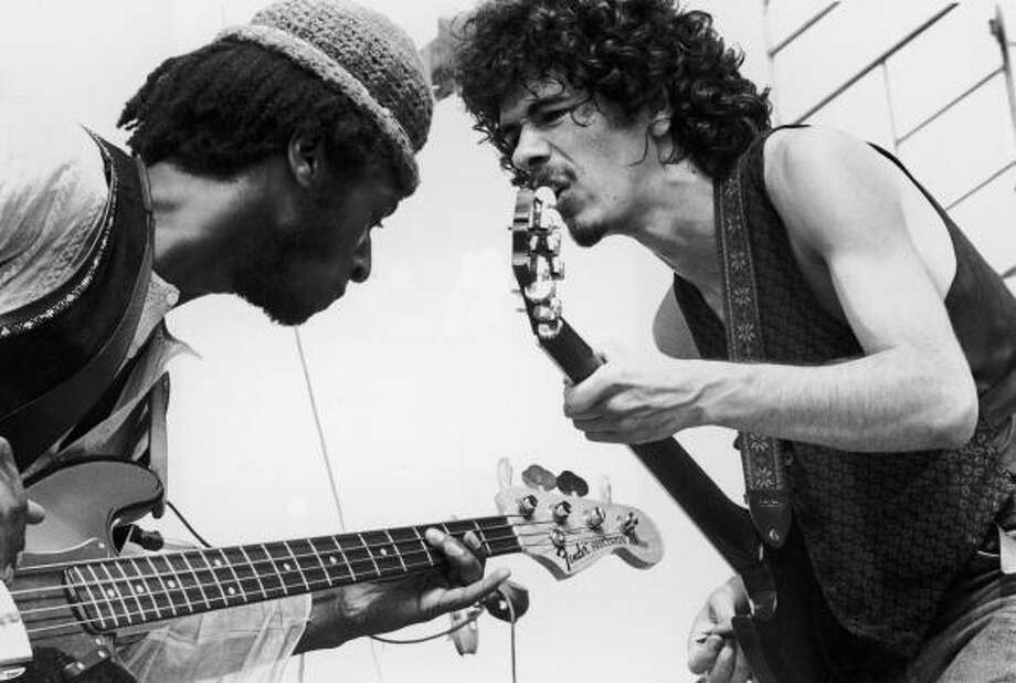 August 1969:  Mexican-born guitarist Carlos Santana (right) and bassist David Brown perform with the group Santana at the Woodstock Music Festival in Bethel, New York. Photo: Tucker Ransom, (Getty Images) / Archive Photos