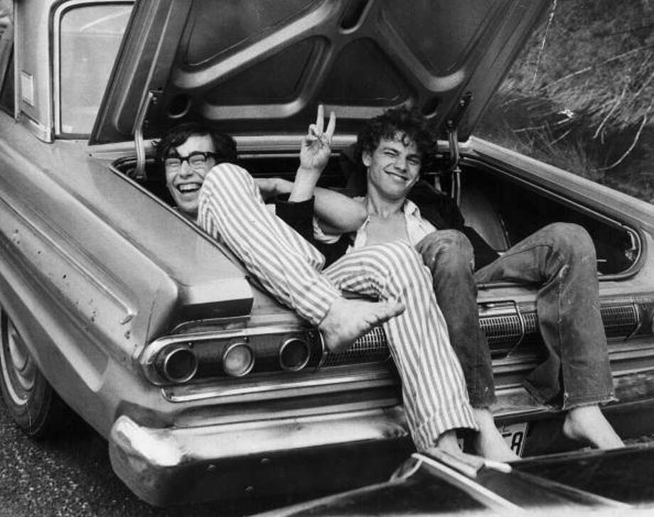 August 1969:  Two young men in the boot of a car after hitching a lift home from the  Woodstock Music and Arts Fair. Photo: Three Lions, (Getty Images) / Hulton Archive