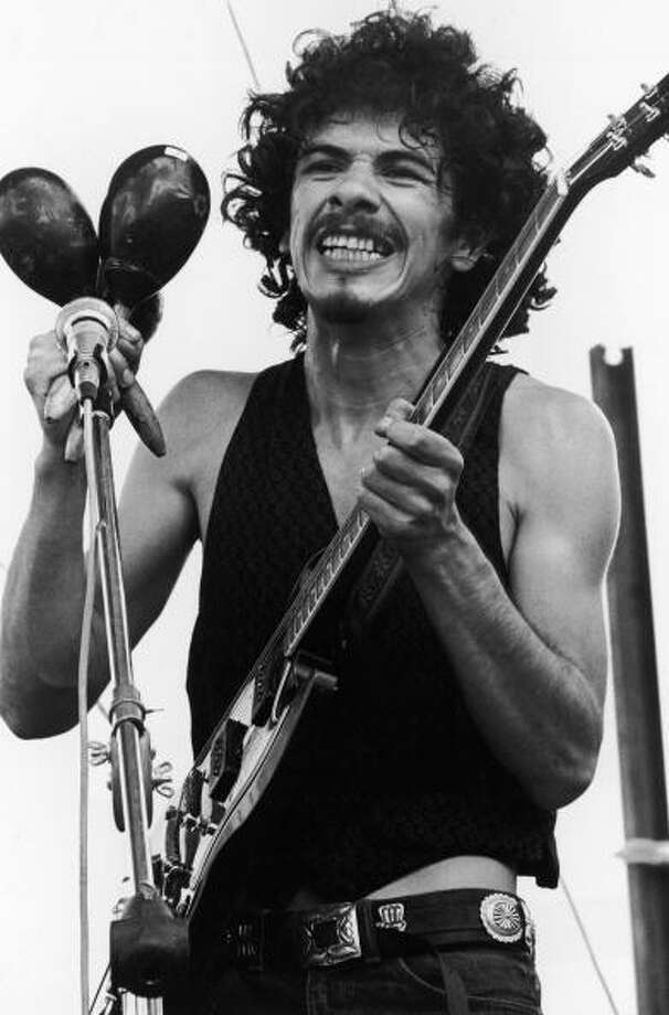 Carlos Santana holds maracas and an electric guitar while performing at the Woodstock Music Festival in Bethel, New York. Photo: Tucker Ransom, Getty Images / Archive Photos