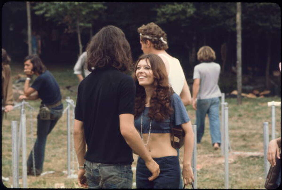 What a smile--two kids in blue--torn jeans, old leather camera bag, blue midriff t-shirt, long hair, amazing smile, at the Woodstock music festival, August 1969.