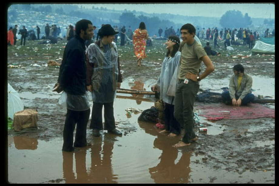 NEW YORK, UNITED STATES - AUGUST 1969:  Young people standing in the mud & water talking, during the Woodstock Music & Art Fair. Photo: John Dominis, Getty Images / Time & Life Pictures