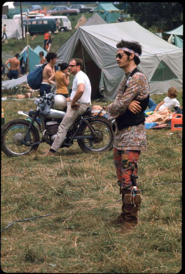 View of an unidentified festival goer as he stands, arms crossed, and watches a performace during the Woodstock Music and Arts Fair, Bethel, New York, August 1969. He is dressed in mis-matched flower print shirt and leggings, a headband made of American flags, a suede vest, and fringed, suede boots, in one of which is a long pipe. Sunglasses, mutton chops, and a mustache complete his outfit. The festival ran from August 15 to 18. Photo: Ralph Ackerman, Getty Images / Hulton Archive