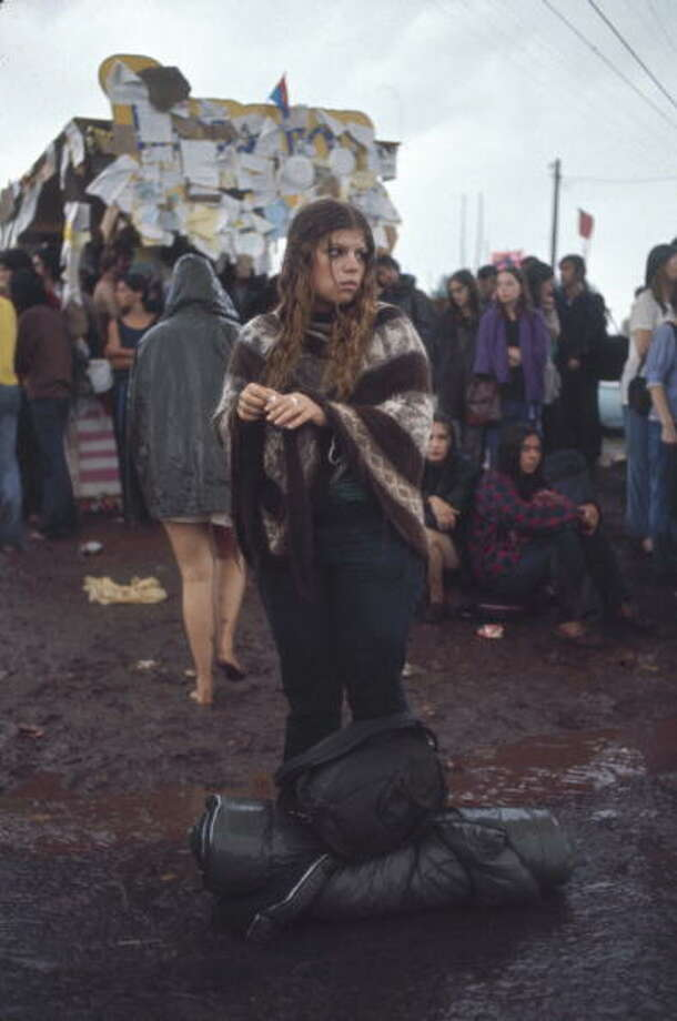 A bedraggled young woman stands in the mud, a sleeping bag and backpack at her feet, on th egrounds of the Woodstock Music and Arts Fair in Bethel, New York, August 15 - 17 (and part of the 18th), 1969. Photo: Bill Eppridge, Getty Images / Time & Life Pictures