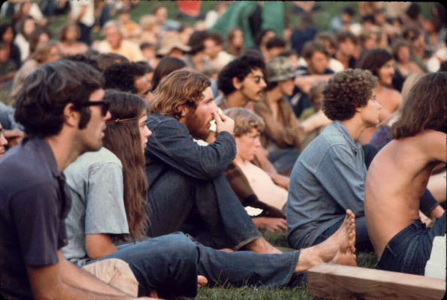 View of the audience as they watch a performance on the 'Free Stage' at the Woodstock Music and Arts Fair, Bethel, New York, August 1969. The 'Free Stage' essentially functioned as both a place from the scheduled performers to jam and as an open mic stage for festival goers. The festival ran from August 15 to 18. Photo: Ralph Ackerman, Getty Images / Hulton Archive