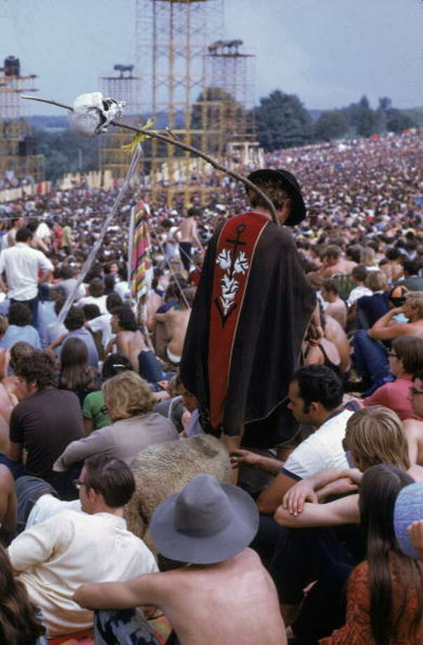 August 1969:  A skull-carrying reveller wanders through the seated crowd during the Woodstock Music and Art Fair in Bethel, New York. Photo: Alon Reininger, Getty Images / Archive Photos