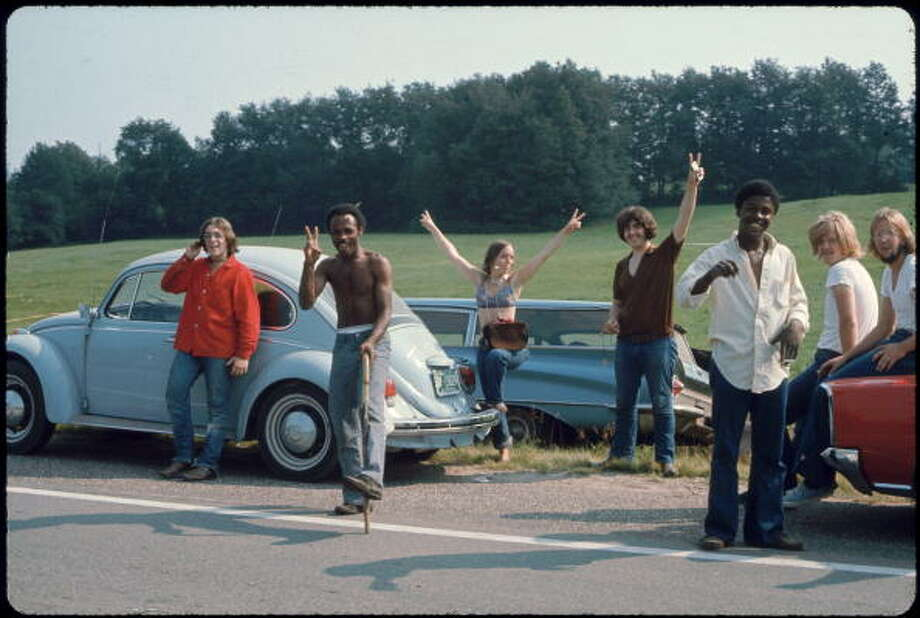 View of a group of people, by several parked cars on the side of the road, on their way to attend the Woodstock Music and Arts Fair, Bethel, New York, August 15, 1969. The festival ran from August 15 to 18. Photo: Ralph Ackerman, Getty Images / Hulton Archive
