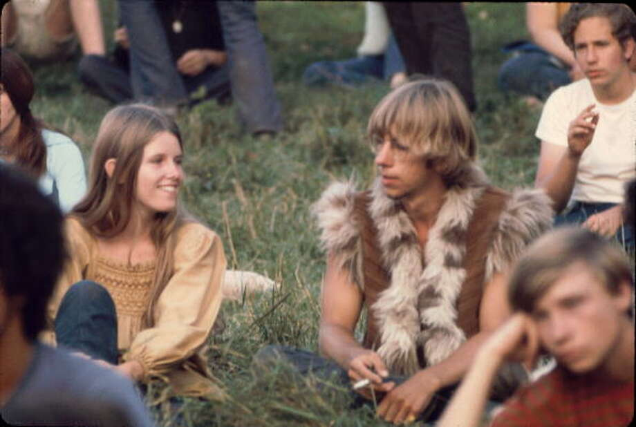 Close-up of a young woman and man, the later dressed in a furry vest, as they sit on the grass near the 'Free Stage' at the Woodstock Music and Arts Fair, Bethel, New York, August 1969. The 'Free Stage' essentially functioned as both a place from the scheduled performers to jam and as an open mic stage for festival goers. The festival ran from August 15 to 18. Photo: Ralph Ackerman, Getty Images / Hulton Archive