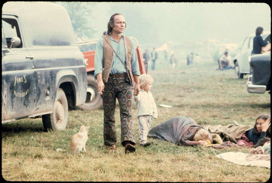 A man and a child walking past people in sleeping bags at the Woodstock music festival, August 1969. Photo: Ralph Ackerman, Getty Images / Copyright 2009 Pat Ackerman