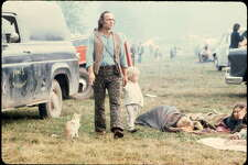 A man and a child walking past people in sleeping bags at the Woodstock music festival, August 1969.