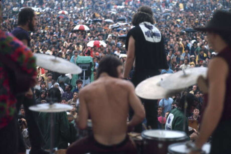 View from the back of the stage as American rock group Country Joe & The Fish perform in the rain at at the Woodstock Music and Arts Fair in Bethel, New York, August 17 1969. Among the visible band members are the arm of Barry Melton (extreme left, in red, green, & blue shirt) and drummer Doug Metzner (shirtless, center). Photo: Bill Eppridge, Getty Images / Time & Life Pictures