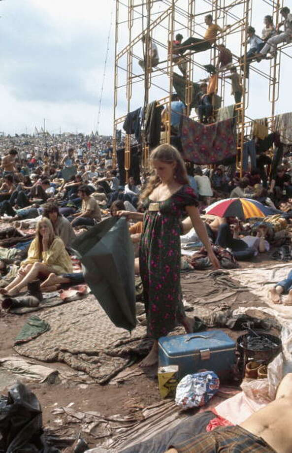 An unidentified woman (possible at festival staffer, due to her ID badge), picks her way barefoot through mud and sleeping bags as she carries a garbage bag at the Woodstock Music and Arts Fair in Bethel, New York, August 15 - 17 (and part of the 18th), 1969. Photo: Bill Eppridge, Getty Images / Time & Life Pictures