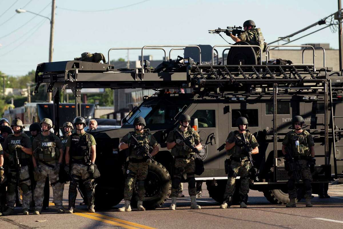 Law enforcement officers, including a sniper perched atop an armored vehicle, watch as demonstrators protest the fatal shooting of Michael Brown, in Ferguson, Mo., Aug. 13, 2014. The police chief of this St. Louis suburb said Wednesday that Brown injured the officer who later fatally shot the unarmed 18 year old - though witnesses dispute that such an altercation occurred. (Whitney Curtis/The New York Times)