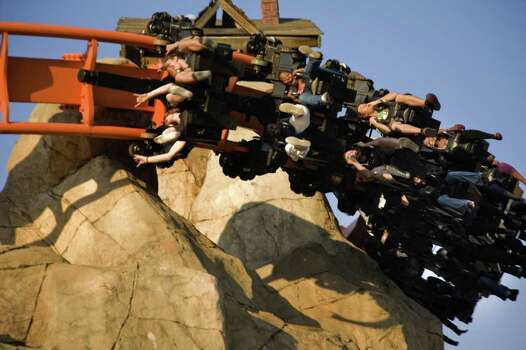 People ride a roller coaster at the Gold Reef Theme Park in Johannesburg, South Africa, in 2010. The park was created around an authentic 19th century gold mine. Photo: GIANLUIGI GUERCIA, AFP/Getty Images / 2010 AFP