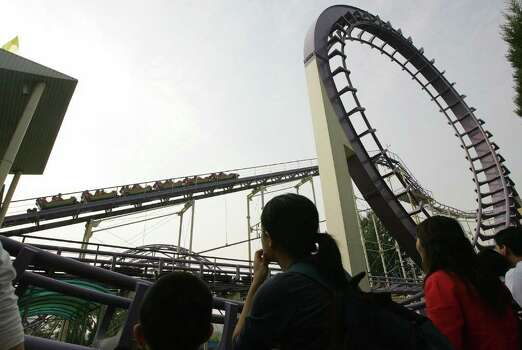 People watch a roller coaster in Beijing, China, in 2007. Photo: FREDERIC J. BROWN, AFP/Getty Images / 2007 AFP