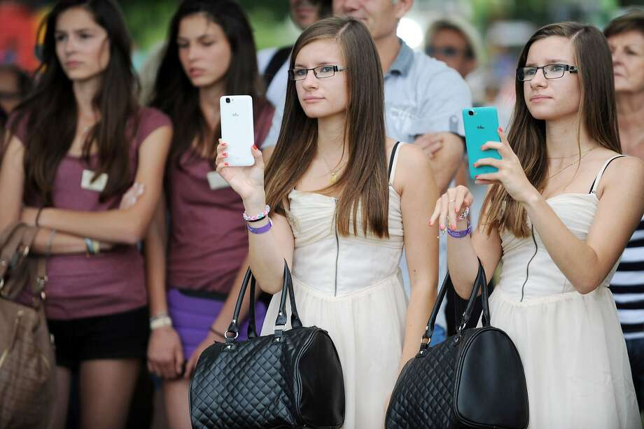 They look alike, they walk alike, at times they even text alike:Sisters attend the Fete des Jumeaux (Festival of Twins), a gathering of twins, triplets and quadruplets, in Pleucadeuc, France. Photo: Fred Tanneau, AFP/Getty Images