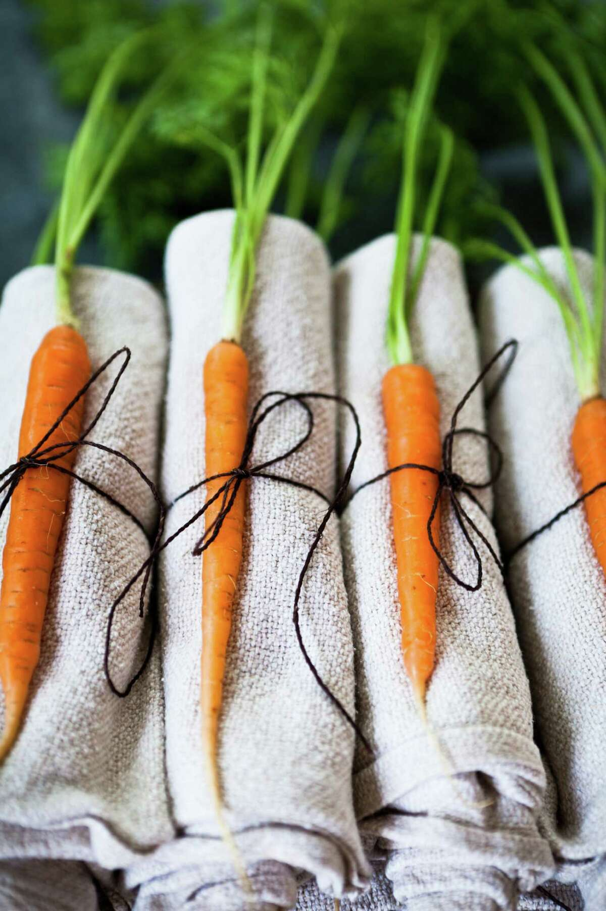 NATURAL NAPKIN FLAIR: Simple, washed hemp napkins get gussied up with tiny baby carrots wrapped in twine. Letting farmers' market produce be the visual hero of your party, you can't go wrong.