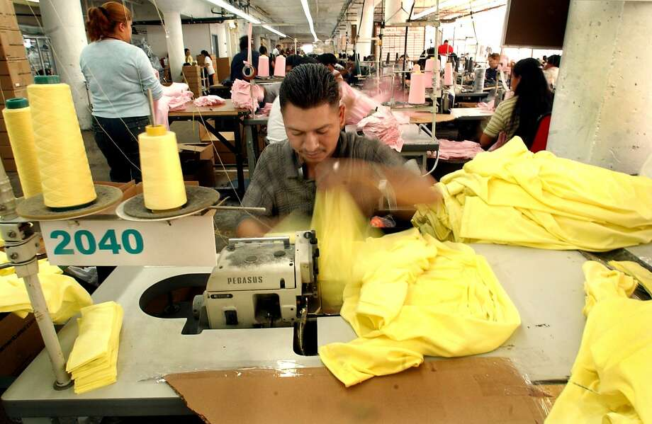A garment worker turns out shirts quickly in American Apparel's Los Angeles factory. The company, which has kept manufacturing in the U.S. as part of its branding to draw customers, below, hasn't turned an annual profit since 2009. Photo: Penni Gladstone, SFC