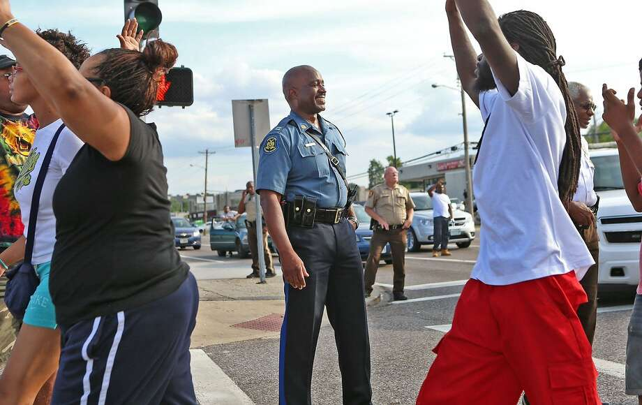 CHANGES THE WORD SEIZED TO TOOK - Capt. Ronald Johnson of the Missouri Highway Patrol smiles at demonstrators march along West Florissant Avenue in Ferguson, Mo., on Thursday, Aug. 14, 2014. The Missouri Highway Patrol took control of a St. Louis suburb Thursday, stripping local police of their law-enforcement authority after four days of clashes between officers in riot gear and furious crowds protesting the death of an unarmed black teen shot by an officer. (AP Photo/St. Louis Post-Dispatch, David Carson) Photo: David Carson, Associated Press