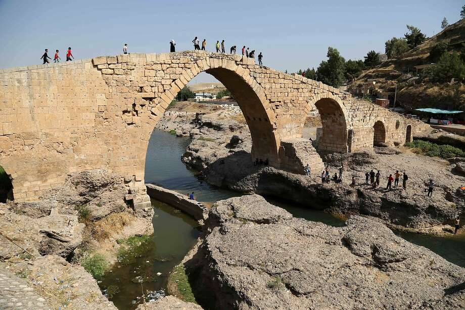 """Displaced Iraqis from the Yazidi community walk on the Delal bridge in Zakho, 300 miles (475 kilometers) northwest of Baghdad, Iraq, Friday, Aug. 15, 2014. The U.N. this week declared the situation in Iraq a """"Level 3 Emergency"""" ? a decision that came after some 45,000 members of the Yazidi religious minority were able to escape from a remote desert mountaintop where they had been encircled by Islamic State fighters. The extremist group views them as apostates and had vowed to kill any who did not convert to Islam. (AP Photo/Khalid Mohammed) Photo: Khalid Mohammed, Associated Press"""