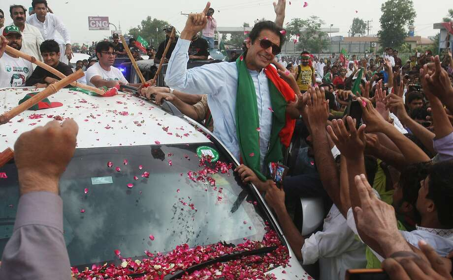 Pakistan's cricketer-turned-politician Imran Khan addresses his supporters Friday, Aug. 15, 2014, in Wazirabad, Pakistan. Supporters of the Pakistani government and opposition protesters clashed on Friday during the second day of a march to the capital, Islamabad, aimed at forcing Prime Minister Nawaz Sharif to resign. (AP Photo/K.M. Chaudary) Photo: K.M. Chaudary, Associated Press