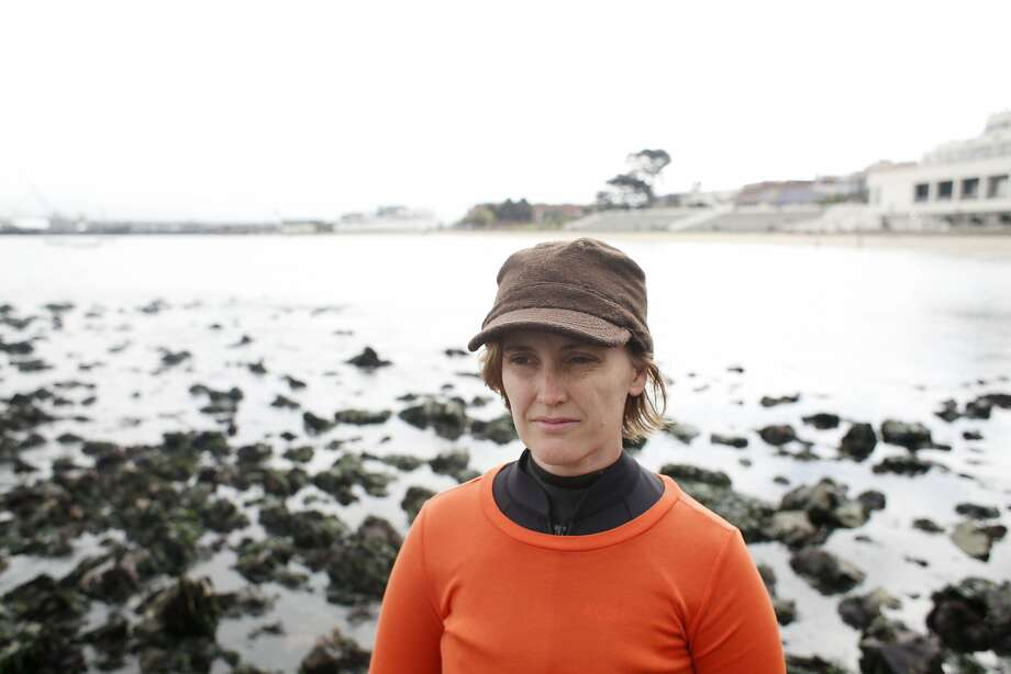 "At western edge of Aquatic Park, New York performance artist Sarah Cameron Sunde stands in the Bay on Friday Aug. 15, 2014 in San Francisco, Calif.  Her intent is to stay for a full cycle of tides, a more-than 13-hour process. The project is called ""36.5: A Durational Performance with the Sea,"" and is meant to raise awareness about rising sea levels. She has done this in other two other times in Bass Harbor, Maine and Akumal, Mexico. Photo: Mike Kepka"