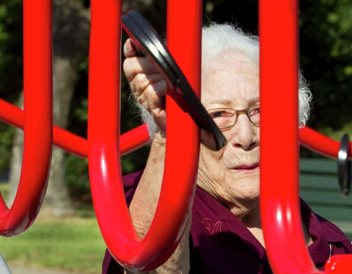 In this photo taken on Wednesday, Aug. 13, 2014, Bertha Pistone, 90, passes a ring across a curved metal structure at an exercise station at the new senior playground at Carbide Park in La Marque, Texas.