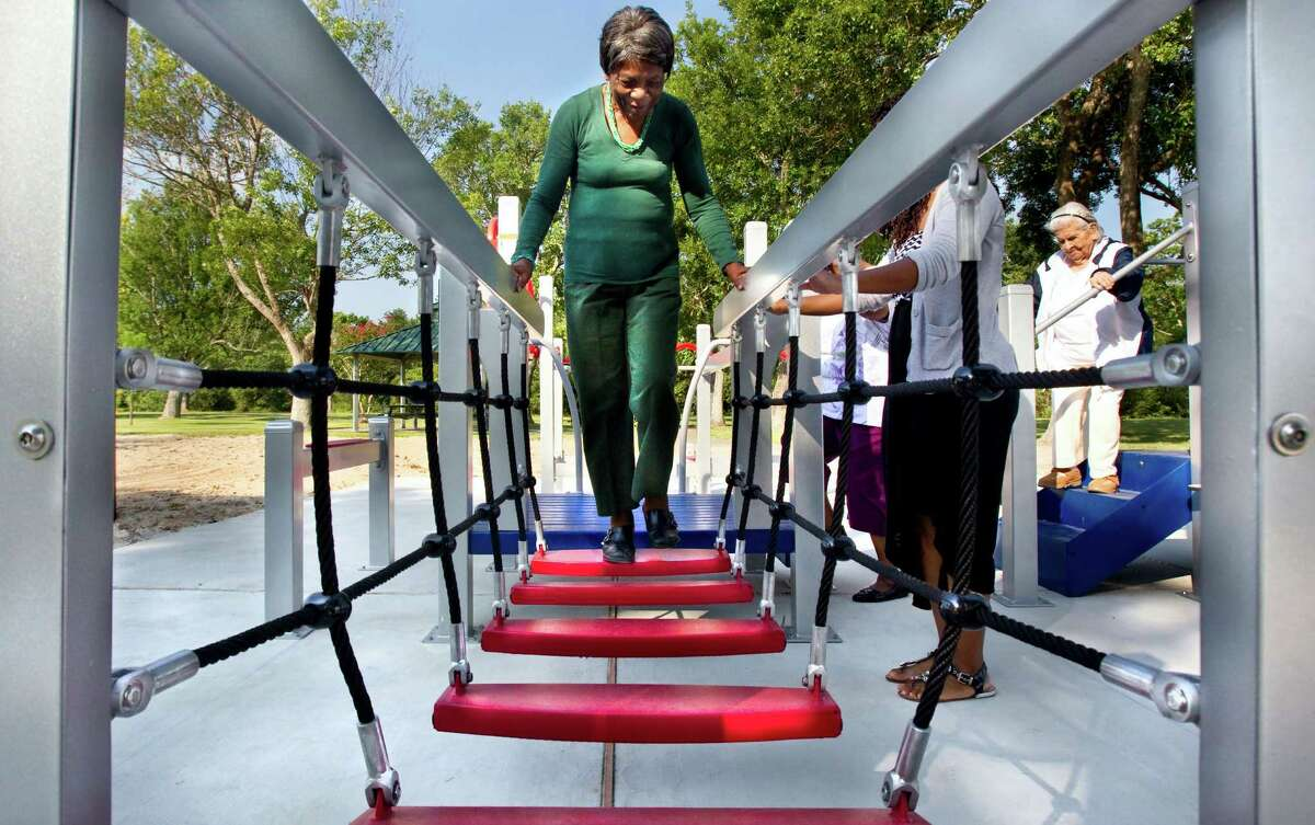 In this photo taken on Wednesday, Aug. 13, 2014, 84-year-old Zady Jones walks across a rope step bridge while trying out the new senior playground at Carbide Park in La Marque, Texas.
