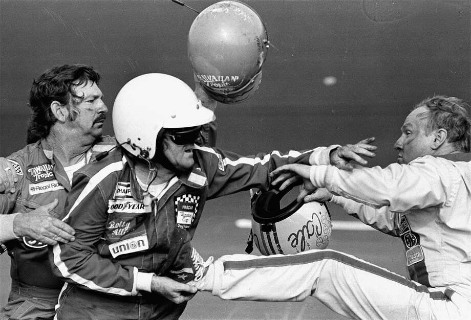 "FILE - In this Feb. 18, 1979 file photo, Bobby Allison holds race driver Cale Yarborough's foot after Yarborough kicked him following an incident on the final lap final lap of the Daytona 500 in Daytona Beach, Fla. NASCAR added a rule Friday, Aug. 15, 2014, ordering drivers to not approach the track or moving cars after accidents. ""Really, we're formalizing rules that have been there,"" Robin Pemberton, NASCAR's vice president of competition and racing development, said at Michigan International Speedway. ""It's reminders that take place during drivers meetings with drivers about on-track accidents. (AP Photo/Ric Feld, File) Photo: Ric Feld, Associated Press"