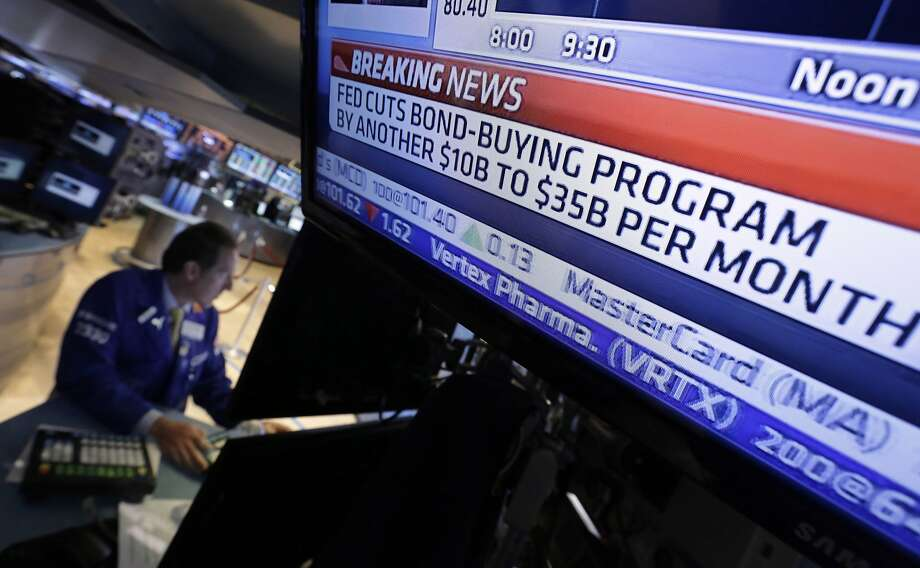 A television monitor at a New York Stock Exchange trading post gives information about a Federal Reserve decision in June. The Fed's low-rate policies have influenced other central banks. Photo: Richard Drew, Associated Press
