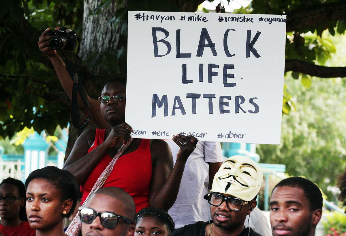 People in a crowd hold signs and listen to speakers at a demonstration on Thursday, Aug. 14, 2014, in Decatur, Georgia, in the town square. The demonstration of more than 200 people was held in response to the shooting death of Michael Brown and following unrest in Ferguson, Missouri. (AP Photo/ Ron Harris)