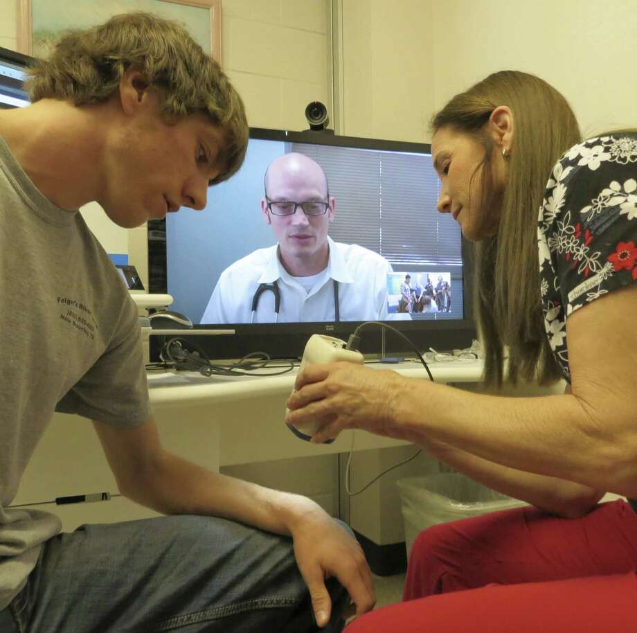 Canyon High School nurse Regina Smith uses a scope to let Dr. Robert Morin (on television screen) remotely examine a cut on the arm of a student. Establishing an interstate telemedicine system is a good idea. Photo: Express-News File Photo / San Antonio Express-News