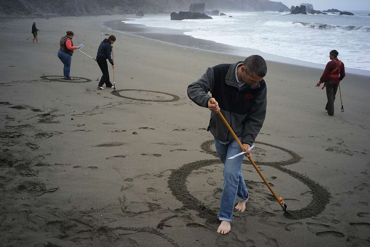 Jake Heath makes memorial art with friends and family of Lindsay Cutshall and her fiance on Friday, Aug. 14, 2014 in Jenner, Calif. Lindsay and her fiance were killed in Jenner ten years ago.