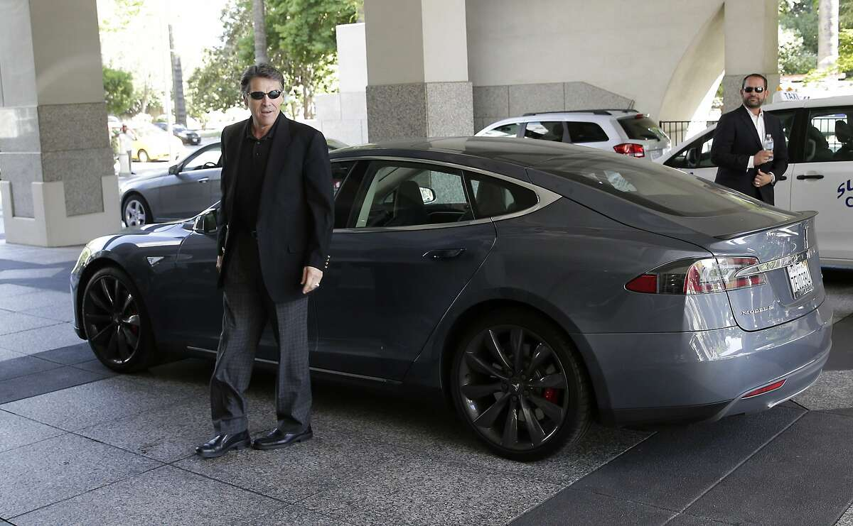 Texas Gov. Rick Perry walks over to talk to reporters after driving up in a Tesla Motors Type S electric car in Sacramento, Calif., Tuesday, June 10, 2014. Perry, the former and potential 2016 Republican presidential candidate, arrived at the meeting with statewide GOP lawmakers and officials across the street from the state Capitol. He is trying to persuade Tesla Motors, based in Palo Alto, to build a $5 billion battery plant in Texas. (AP Photo/Rich Pedroncelli)