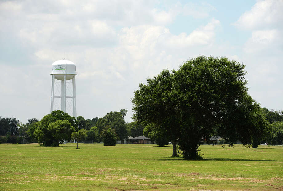 "A water tower decorated with a sign reading ""The Patch Golf Course"" overlooks the former course in Groves on Wednesday. The space is slated to become a 124-home gated community. The city of Groves has added more than 200 homes to it's stock in the last eight years. Photo taken Wednesday 8/13/14 Jake Daniels/@JakeD_in_SETX Photo: Jake Daniels / ©2014 The Beaumont Enterprise/Jake Daniels"