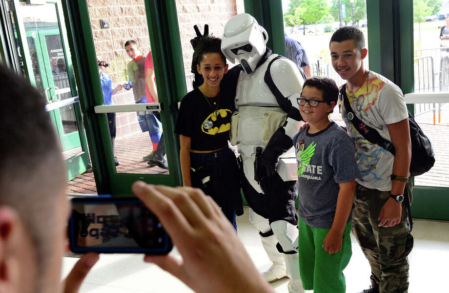An Imperial Storm Trooper jokes around with with Ashley Palomares, 14, of Bridgeport, Ryan Marrero, 10, and their uncle Victor Gonzalez, during Connecticut ComiCONN at the Webster Bank Arena in downtown Bridgeport, Conn. on Friday, August 15, 2014. Snapping the photo is Luis Morales, 15. ComiCONN continues through Sunday. Photo: Christian Abraham / Connecticut Post