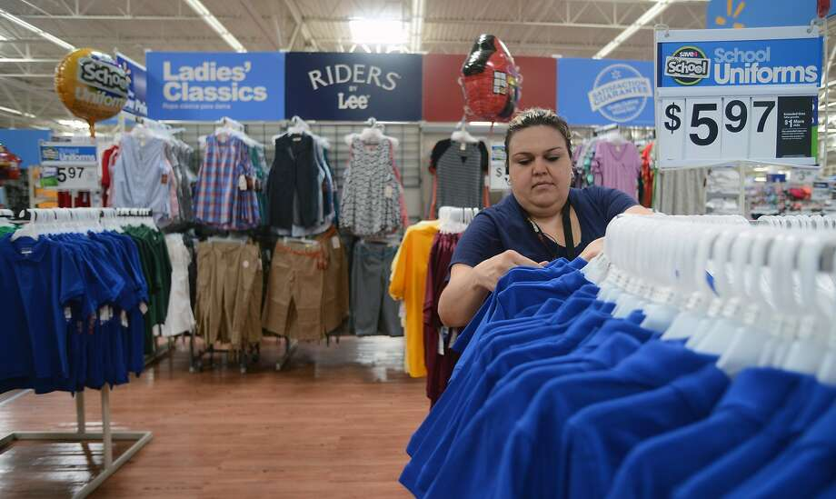Walmart employee Nidia Flores arranges shirts in Brownsville, Texas. The company has pledged to spend on items made in America. Photo: Brad Doherty, Associated Press