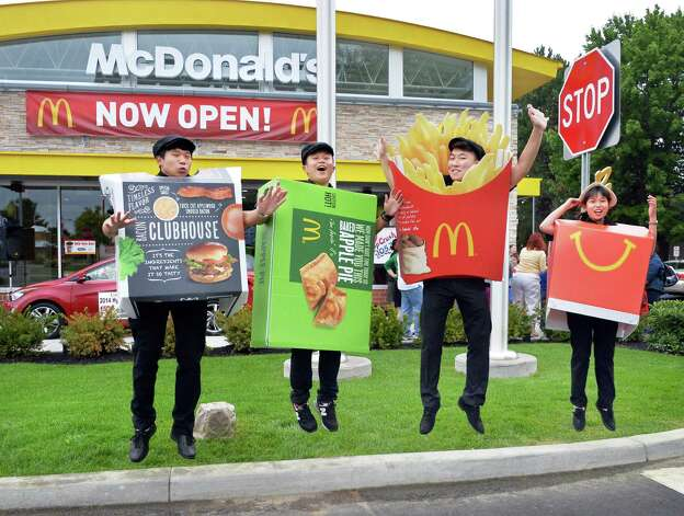 McDonald's employees, from left, Poly Wu, Jerry Yang, Hu Nan and Rebecca Xiong greet customers during the grand re-opening of the Wolf Road McDonald's Friday August 15, 2014, in Colonie, NY.  (John Carl D'Annibale / Times Union) Photo: John Carl D'Annibale / 00028126A