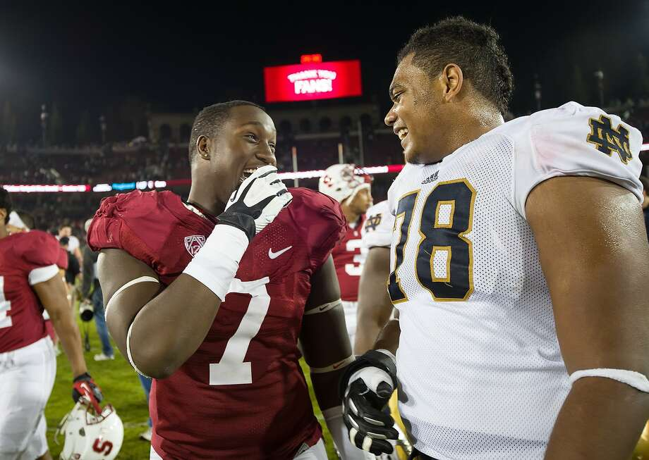 STANFORD, CA - November 30, 2013: Aziz Shittu of the Stanford football team talks to a Notre Dame player after their game. The Stanford Cardinal vs the Notre Dame Irish at Stanford Stadium in Stanford, CA. Final score Stanford Cardinal 27, Notre Dame Irish 20.  STANFORD, CA - November 30, 2013: The Stanford Cardinal vs the Notre Dame Irish at Stanford Stadium in Stanford, CA. Final score Stanford Cardinal 27, Notre Dame Irish  20. Photo: David Bernal, Stanfordphoto.com