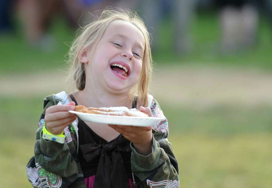 Angie Covillion, 7, of New Milford, laughs while eating fried dough at the 63rd annual Bridgewater Country Fair in Bridgewater, Conn. Friday, Aug. 15, 2014.  The fair, sponsored by the Bridgewater Volunteer Fire Department, features food, kids games, and many events such as a parade, a tractor pull, musical performances and motocross demonstrations.  Admission is $8 for adults and free for children under 12 as the fair continues Saturday from 8 a.m. to 11 p.m. and Sunday from 8 a.m. to 6 p.m. Photo: Tyler Sizemore / The News-Times
