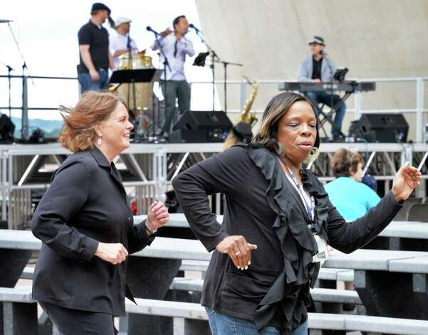 Co-workers Elizabeth Brown, left, of East Greenbush and Claudia Brown of Delmar, unrelated, dance to Sensemaya's Made in the Shade of the Egg performance at the Empire State Plaza Friday. Aug. 15, 2014, in Albany, NY.  (John Carl D'Annibale / Times Union) Photo: John Carl D'Annibale / 00028201A
