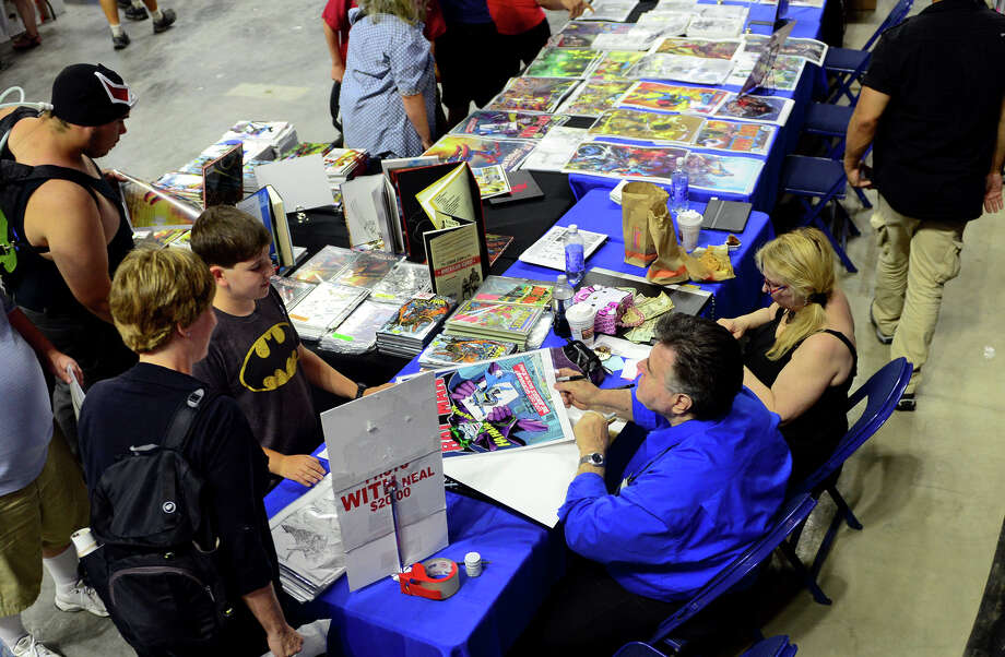 Legendary comic book artist Neal Adams signs autographs for Aaron Gruen, 11, of Weston, during Connecticut ComiCONN at the Webster Bank Arena in downtown Bridgeport, Conn. on Friday, August 15, 2014. Photo: Christian Abraham / Connecticut Post