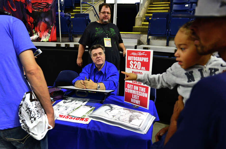 Legendary comic book artist Neal Adams signs autographs for his fans during Connecticut ComiCONN at the Webster Bank Arena in downtown Bridgeport, Conn. on Friday, August 15, 2014. Standing behind Neal is son Joel. ComiCONN continues through Sunday. ComiCONN continues through Sunday. Photo: Christian Abraham / Connecticut Post