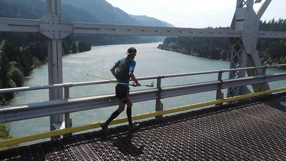 Joe McConaughy crosses the Bridge of the Gods into Washington while completing the Pacific Crest Trail in record time. Photo: RunForColin.com