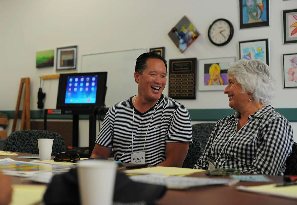 Instructor Sue Ewing has a laugh with Derrick Wong during a group therapy session at the Aphasia Center of California on August 05, 2014 in Oakland, CA. Aphasia is a condition that usually follows a stroke or other brain injury and impairs a person's ability to communicate. The center helps people with aphasia through group therapy and other classes that encourage social interaction