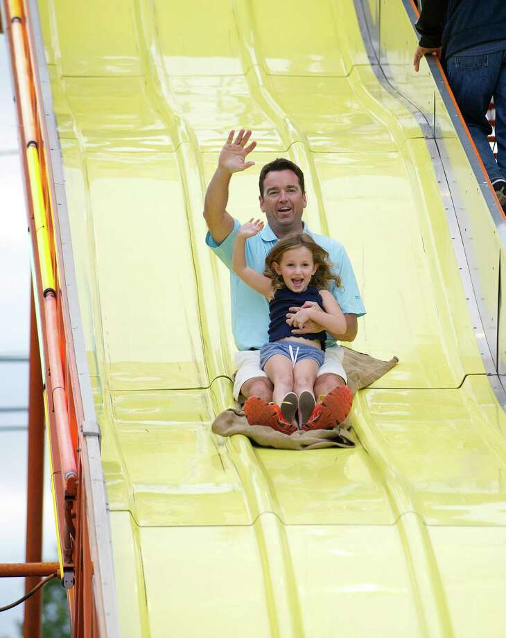 Katherine Allard, 5, and her father, Matt, wave to their family as the descend the slide during the St. Catherine of Siena Church carnival in Greenwich, Conn., on August 15, 2014. Photo: Lindsay Perry / Stamford Advocate