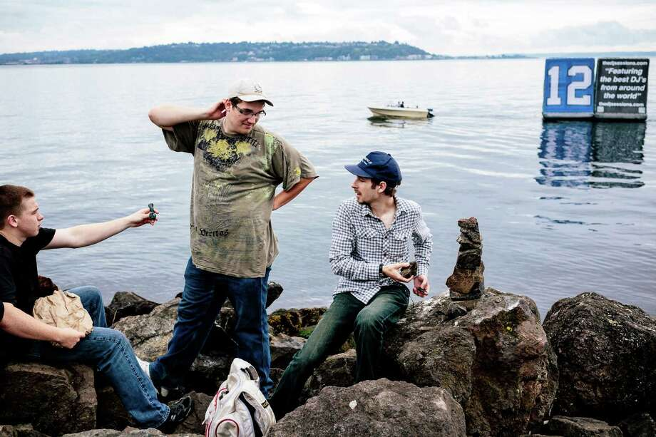 From their spot on the rocks overlooking Puget Sound, Matt Leeson, left, hands off a pipe to friend Chase Dumas, center, while chatting with Sam Pingree, right, on the first of three days of Hempfest, Seattle's annual gathering to advocate the decriminalization of marijuana Friday, August 15, 2014, at Myrtle Edwards Park on the Seattle waterfront in Seattle, Washington. The three-day annual political rally, concert, and arts and crafts fair continues through Sunday. Photo: JORDAN STEAD, SEATTLEPI.COM / SEATTLEPI.COM